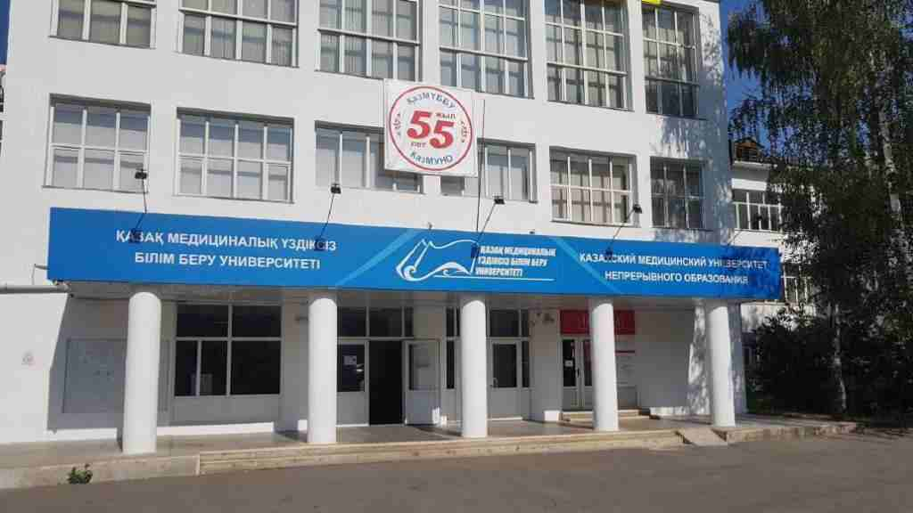 White building with blue board and entrance of Kazakh Medical University of Continuing Education